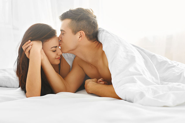 happy couple lying in bed kissing